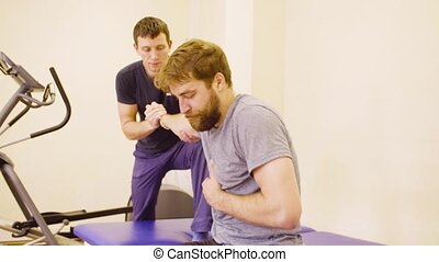 Doctor physiotherapist helping the patient to do the exercise