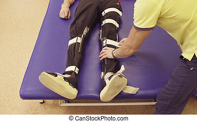 Doctor physiotherapist putting the orthosis for disabled man