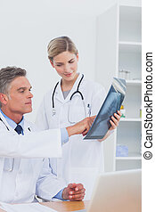 Doctor pointing a radiography to his colleague