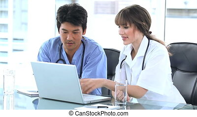 Doctor pointing at the screen of a laptop with a colleague