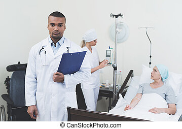 Doctor posing against the background of the patient. He holds a paper tablet in his hands.