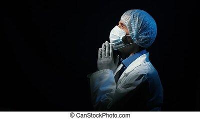 Doctor praying at the dark room