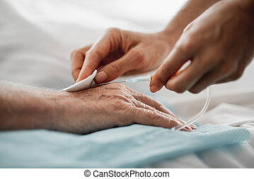 Doctor preparing patient hand for intravenous drip