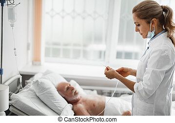 Doctor preparing system for intravenous drip while patient resting