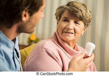 Doctor prescribing senior woman medicament