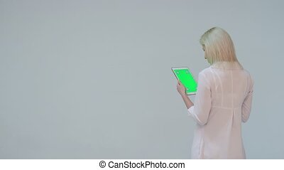 Doctor pressing the green screen of a tablet computer against
