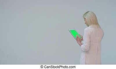 Doctor pressing the green screen of a tablet computer against white background