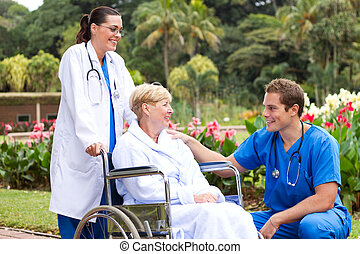 doctor pushing wheelchair patient