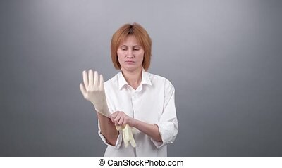Doctor put on latex medical gloves, closeup. COVID-19.
