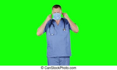 Doctor puts a medical bandage on face. Green screen