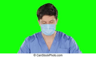 Doctor puts on stethoscope. Green screen