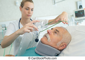 doctor putting oxygen mask on a senior patient