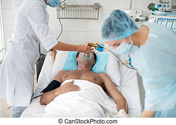 Doctor putting oxygen mask on patient in intensive care ward