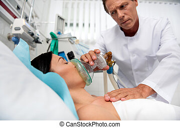 Doctor putting oxygen mask on young lady and monitoring her condition