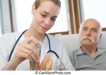 Doctor putting pulse reader on patient's finger