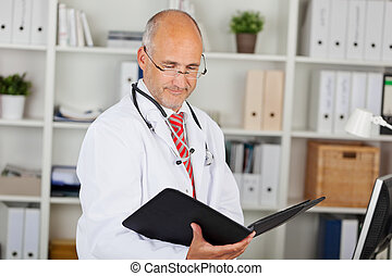 Doctor Reading Folder Against Shelves In Office