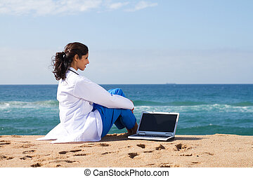 doctor relaxing on beach with laptop by her side