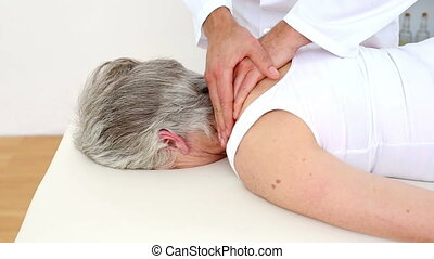 Doctor rubbing senior patients shoulders at the...