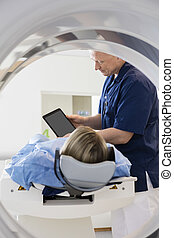 Doctor Showing Digital Tablet To Patient Undergoing CT Scan