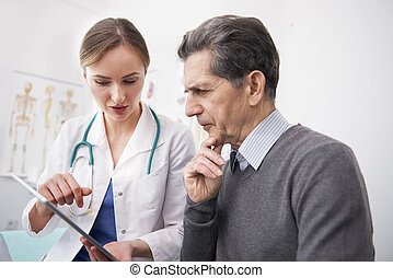 Doctor showing examination results on the digital tablet