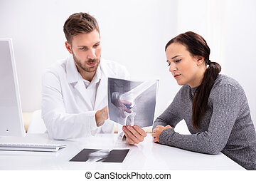 Doctor Showing Knee X-ray To Patient