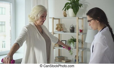 Doctor showing light exercises to pensioner lady at her house