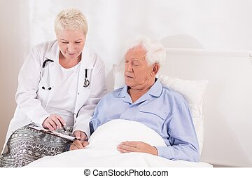 Doctor showing medical test resulst to her elder patient