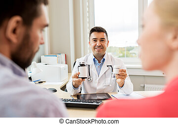 doctor showing medicine to family couple at clinic