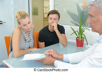 Doctor showing paperwork to couple in office