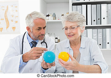 Doctor showing stress buster balls to senior patient
