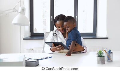 doctor showing tablet pc to baby patient at clinic -...