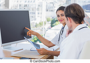 Doctor showing the screen of a computer to a colleague while...