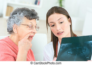 Doctor showing x-ray to senior lady