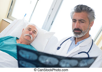 doctor showing xray to a senior patient in hospital