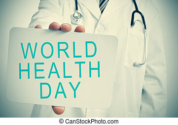 doctor shows a signboard with the text world health day
