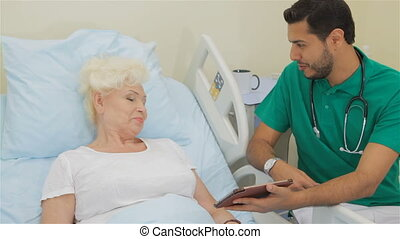 Doctor shows something on his tablet to female patient