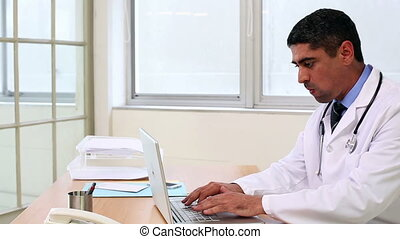 Doctor sitting at desk typing on laptop