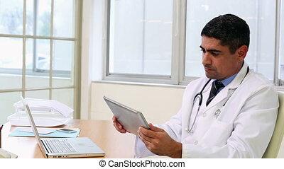 Doctor sitting at desk using tablet