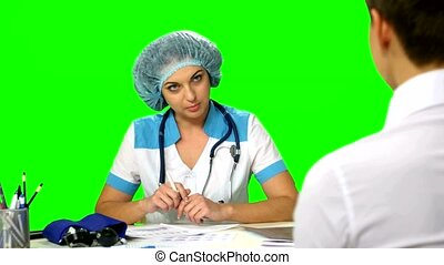 Doctor sitting at the table explains  diagnosis of a young woman. Green screen.