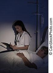 Doctor sitting by elderly patient