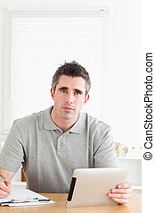 Doctor sitting working with a tablet and a chart