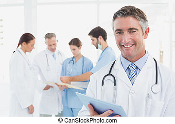 Doctor smiling at the camera as he uses a tablet