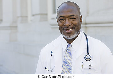 Doctor Smiling To Camera - Doctor Standing Outside With...