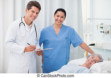 Doctor smiling while holding a clipboard in hospital ward