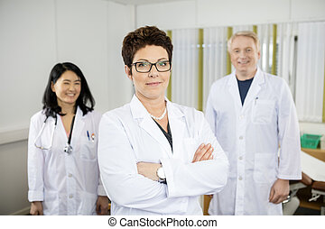 Doctor Standing Arms Crossed While Colleagues Smiling In Clinic