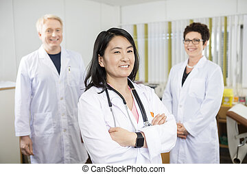 Doctor Standing Arms Crossed While Coworkers Smiling In Clinic