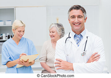 Doctor standing arms crossed with nurse and patient in...