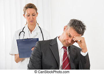 Doctor Standing Behind The Businessman Having Headache