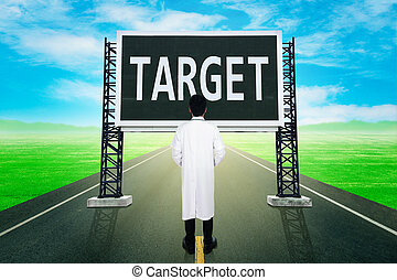 doctor standing on road and looking with large sign of target