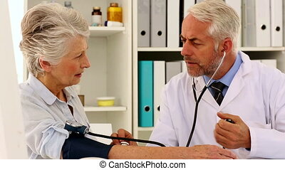Doctor taking blood pressure of his